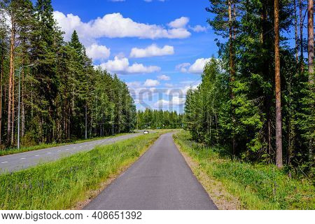 Asphalt Road And Bike Path In Finland. Beautiful Summer Landscape With Forest And Blue Sky.