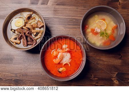Set Of Serving Asian Soups On Gray Background Top View. Tom Yum Soup, Eel Fish Soup And Ramen Noodle