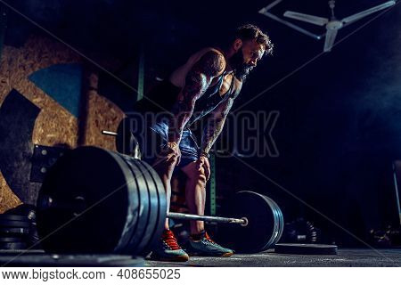 Muscular Fitness Man Preparing To Deadlift A Barbell In Modern Fitness Center. Functional Training.