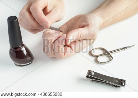 Woman Hands Doing Manicure. Female Hands, Holding Nail File, With Nail Polish, Scissors And Nail Cli