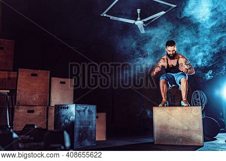 Fit Tattoed Bearded Man Jumping Onto A Box As Part Of Exercise Routine. Man Doing Box Jump In The Gy