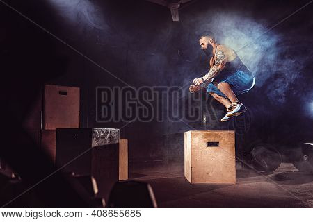 Athlete Gave Exercise. Jumping On The Box. Phase Touchdown. Gym Shots In The Dark Tone. Smoke In Gym