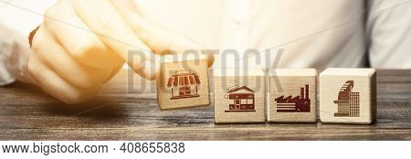 A Man Lays In A Row Blocks With Symbols Of Business Shops, Offices And Factories. Building A Success