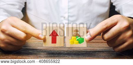 Businessman Holds Blocks With Up Arrow And Money. Concept Of Business Success, Financial Growth And