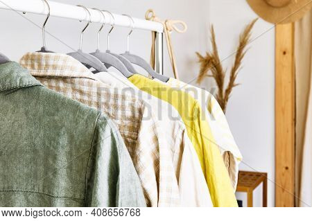 Linen Clothes On Gray Hangers On The Clothes Rack. Slow Fashion. Conscious Consumption. Crisis In Th