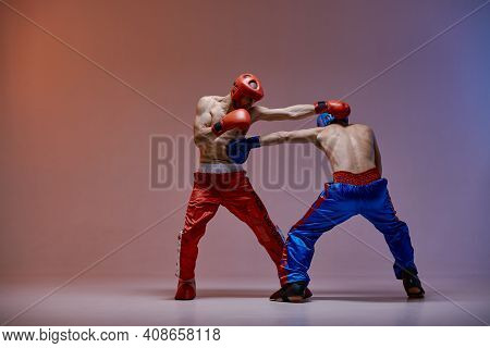 Jab Of Fighting Athletic Males In Boxing Gloves With Bare Fit Torsos In Red Light In Studio, Martial