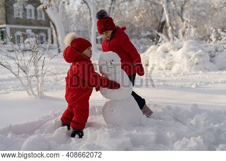 Two Sisters In Red Jackets And Hats Are Making A Snowman In A Winter Park. In Winter, Children Play