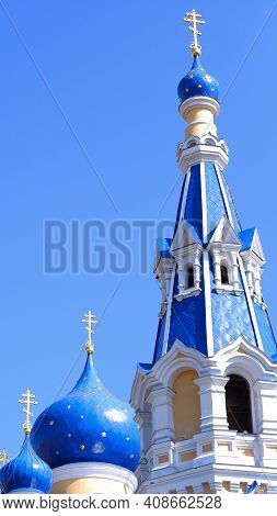 A Church With Blue Domes Against A Clear Blue Sky On A Sunny Day. Orthodox Cross On The Dome Of Chur