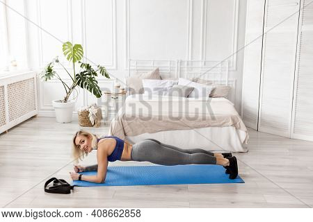 A Sportive Attractive Woman Doing Yoga, Doing Exercises Or Push-ups, Stands On Bent Arms In A Plank