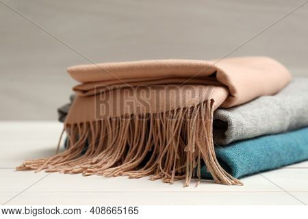 Stack Of Cashmere Clothes On Wooden Table, Closeup