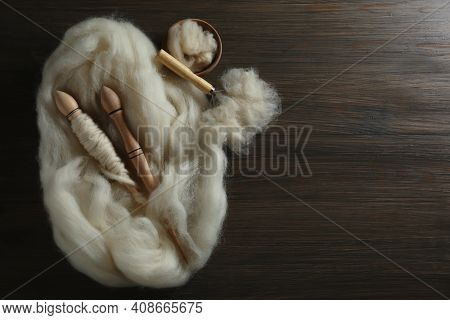 Soft White Wool, Spindles And Comb On Wooden Table, Flat Lay. Space For Text
