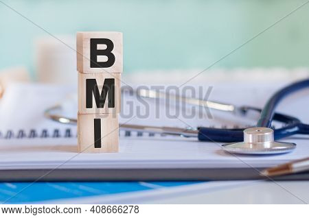 The Word Bmi Is Written On Wooden Cubes Near A Stethoscope On A Paper Background. Bmi - Body Mass In