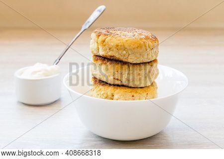 Homemade Cottage Cheese Pancakes Syrniki Stack On Round Glossy White Bowl, Sauce Pan, Sour Cream, Sp