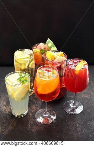A Set Of Various Glasses Full Of Colorful Lemonades With Ice Cubes, Mint Sprig, Lemon, Orange And Wa