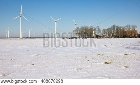 Dutch Farmland Covered By White Snow With Farmhouse And Wind Turbines