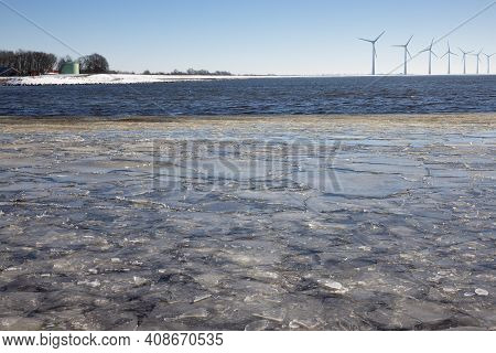 Dutch Winter With View At Sea Covered With Drift Ice And Waves