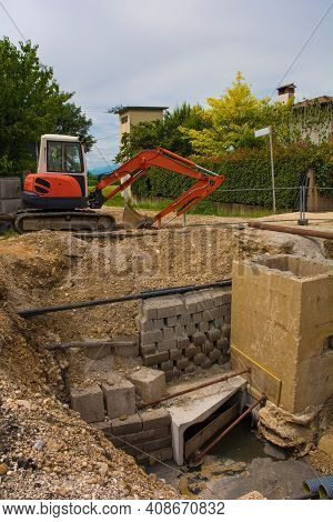 A Sewer Well Trench And A Compact Crawler Excavator With A Rotating House Platform And Continuous Tr