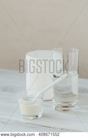 Collagen Powder In Bowl, Glass Of Water And Spoon On White Wooden Background. Extra Protein Intake.