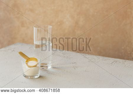 Collagen Powder In Bowl, Glass Of Water And Measure Spoon On White Wooden Background. Extra Protein