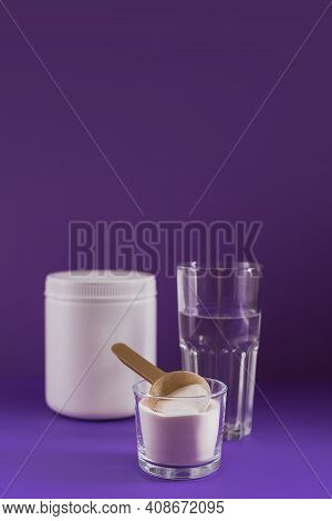 Collagen Powder In Bowl, Glass Of Water And Measure Spoon On Purple Background. Extra Protein Intake