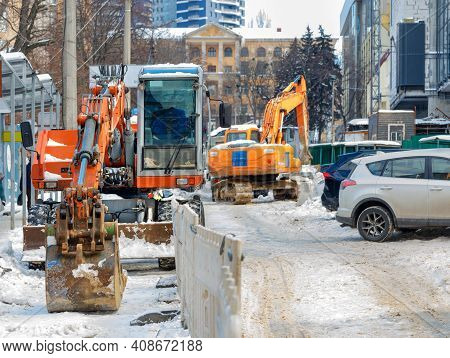 Large Excavators With Metal Buckets Clear The Roadway Of A City Street From An Abundance Of Snow. Se