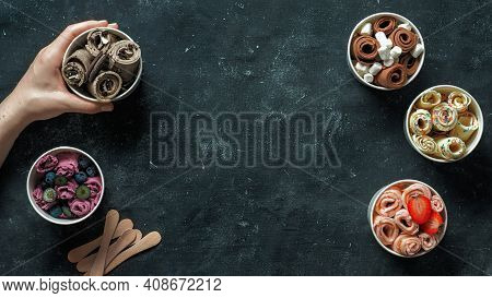 Hand With Rolled Ice Cream In Cone Cup On Dark Background. Different Iced Rolls Top View Or Flat Lay