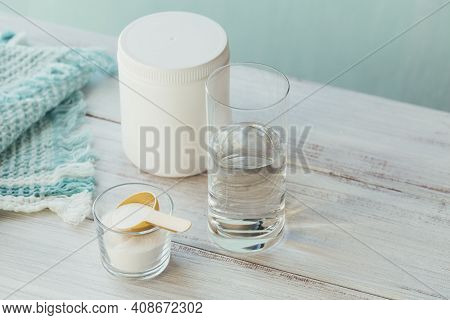 Collagen Powder In Bowl, Glass Of Water And Measure Spoon On Light Blue Background. Extra Protein In
