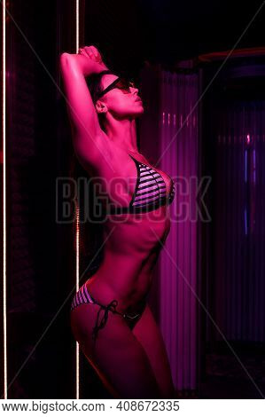 Neon Light And Sexy Girl. Beautiful And Athletic Woman With Naked Healthy Body Standing In Solarium
