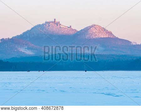 Bezdez Castle Above Frozen Machovo Lake With Ice Skating Or Walking People. Winter Landscape, Freeze