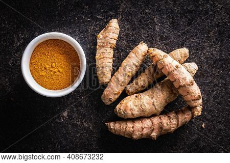 Indian turmeric powder and root. Turmeric spice. Ground turmeric in bowl on black table. Top view.
