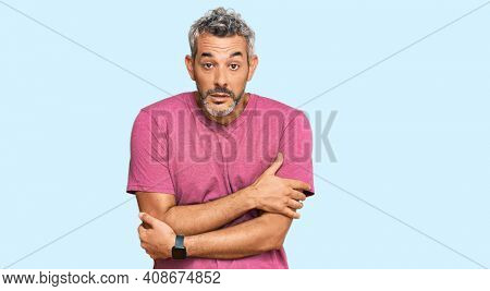 Middle age grey-haired man wearing casual clothes shaking and freezing for winter cold with sad and shock expression on face