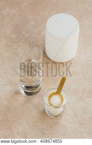 Collagen Powder In Bowl, Glass Of Water And Measure Spoon On Light Beige Background. Extra Protein I