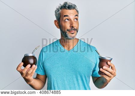 Middle age grey-haired man drinking mate infusion smiling looking to the side and staring away thinking.