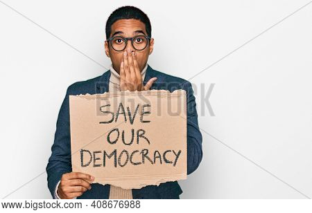Young handsome hispanic man holding save our democracy protest banner covering mouth with hand, shocked and afraid for mistake. surprised expression