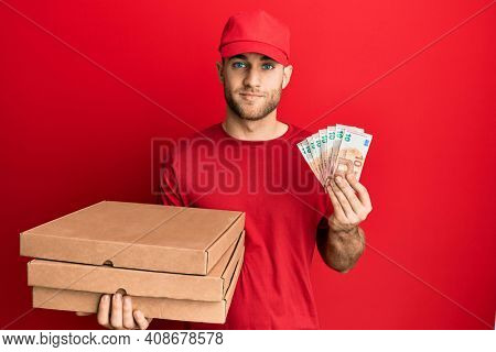 Young caucasian man holding take away food and 10 euros banknotes relaxed with serious expression on face. simple and natural looking at the camera.