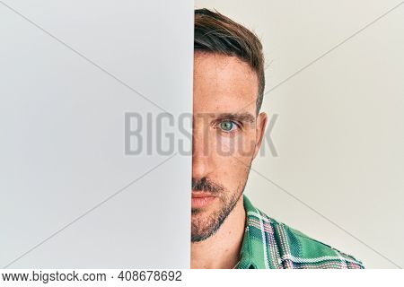 Handsome man with beard holding blank empty banner covering half face relaxed with serious expression on face. simple and natural looking at the camera.