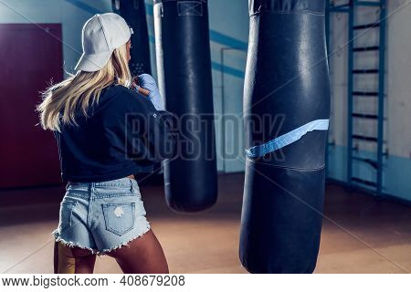 Concentrated Blonde Woman Doing A Fitness Boxing Workout With A Punching Bag. The Girl In The Boxing