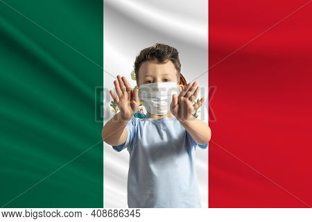 Little White Boy In A Protective Mask On The Background Of The Flag Of Mexico. Makes A Stop Sign Wit