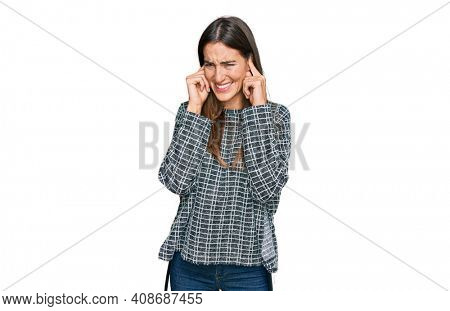 Young beautiful woman wearing casual clothes covering ears with fingers with annoyed expression for the noise of loud music. deaf concept.