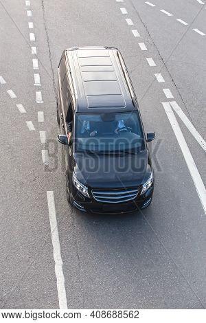 Black Minivan Moves On Urban Multi-lane Road