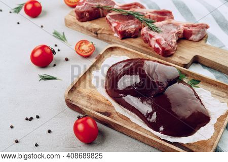 Raw Beef Liver And Beef Steaks On Wooden Cutting Board