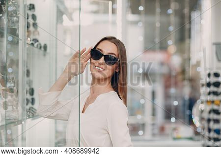 Close Up Of Gorgeous Young Smiling Woman Smiling Picking And Choosing Glasses At The Optician Corner