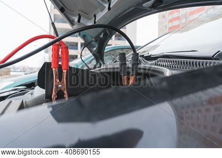 Jump Cables On Car Low Power Battery. Black And Red. Broken Car Start Attempt. Selective Focus.
