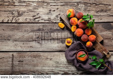 Peaches With Leaves On Dark Wooden Board With Peach In Halves. Composition With Ripe Juicy Peaches.