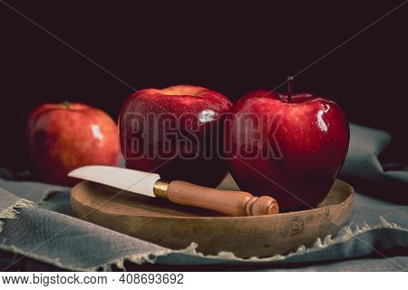Still Life With Red Delicious Apples On A Wooden Plate. Three Ripe Apples On A Wooden Plate And A Gr