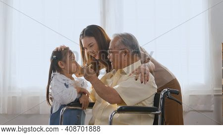 Asian Happy Disabled Elderly In Wheelchair With Daughter And Granddaughter Smiling Playing Together