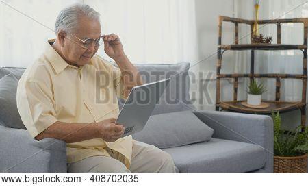 Senior Man Dressed To Wear Eyeglasses Sitting On Sofa Looking News On Digital Tablet Computer In Liv