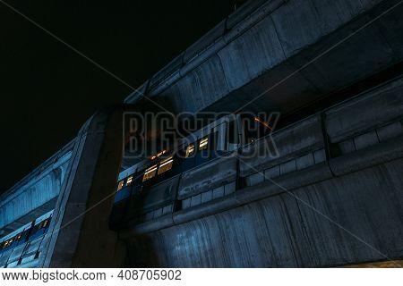 Bts Train Car Arriving On Massive Concrete Tracks At Night.