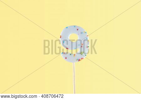 Number 9 Shaped Lolipop On Yellow Background. Anniversary Selebration, Birthday Party. Kids Sweet Nu