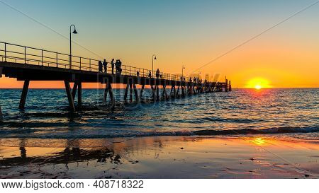 Glenelg Beach Beach Foreshore View With People Walking Along The Pier At Sunset, South Australia